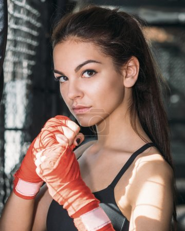 Portrait of a beautiful woman with the boxing gloves in gym