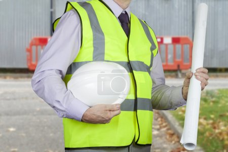 Site engineer in high visibility vest holding drawings