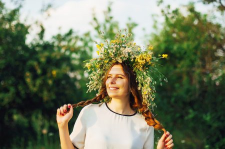 beautiful girl in wreath of flowers  in meadow on sunny day. Portrait of Young beautiful woman wearing a wreath of wild flowers. Young pagan Slavic girl conduct ceremony on Midsummer.