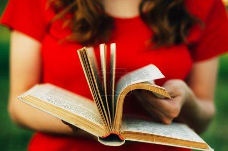 Photo pour Détail d'une femme lisant un livre. Gros plan d'une femme tenant un vieux livre à l'extérieur. femme tenant un livre derrière une toile de fond de nature. Des mains féminines tenant un vieux livre. femme lisant un livre - image libre de droit