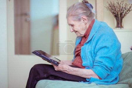 Una mujer mayor está hablando a través de una tableta, una abuela moderna, un surfista de plata, sentado en casa, los jubilados se quedaron en casa seguros durante la cuarentena, la comunicación en línea en Internet.