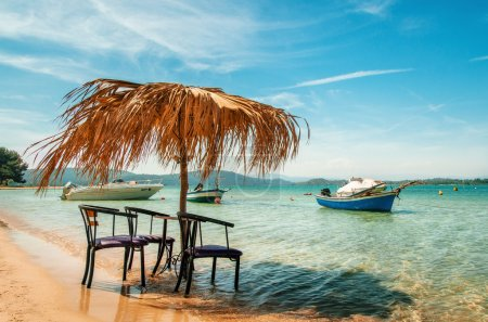 Chairs under thatched umbrellas in a turquoise sea