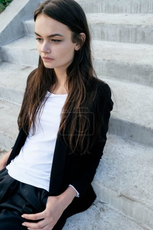 Beautiful young girl on a city street. Dressed in men's style