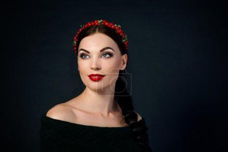 Photo pour Portrait de souriante jeune belle brune avec guirlande rouge et tresse sur fond foncé - image libre de droit