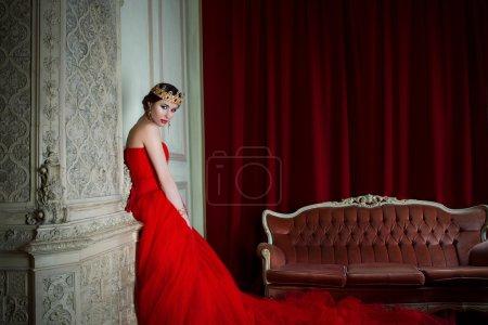 Photo pour Belle fille en robe longue rouge et dans la Couronne royale près de cheminée dans un habitacle en studio photo - image libre de droit