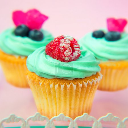 Cupcakes with butter cream and vanilla with raspberry and blueberry