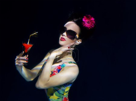 beautiful girl in a colorful stylish swimsuit and sunglasses and pink gerbera in the head with a cocktail  in her hand underwater in the swimming pool