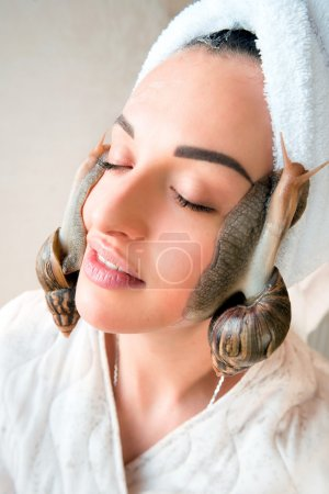 portrait of young darkhaired woman with snails achatina giant on her face