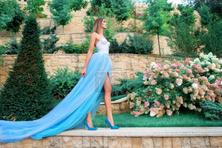 portrait of young beautilul woman in long blue dress in magic blooming park