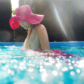 Smiling Young beautiful white woman in dress and pink hat underwater in the swimming pool