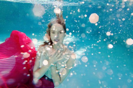 Smiling Young beautiful white woman in dress underwater in the swimming pool