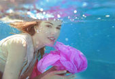Young beautiful white woman in dress with pink flower underwater in the swimming pool