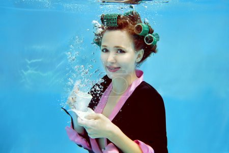 young girl in a bathrobe and curlers  underwater in the swimming pool
