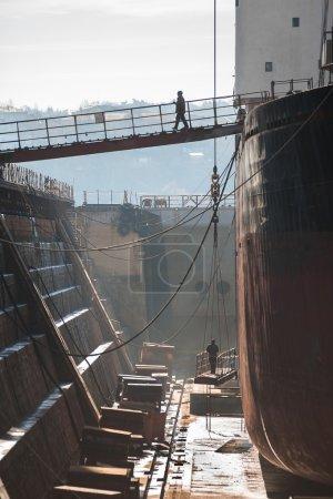 Shipyard workers in dry dock.