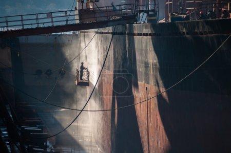 Shipyard worker power washing a ship on dry dock.