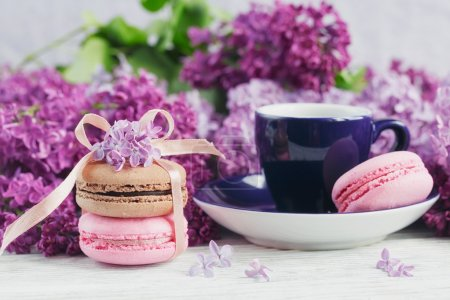 Cup of black coffee, lilac flowers and sweet pastel french macar