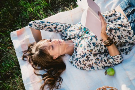 Girl lying in the park and reading