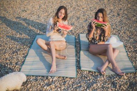 Girlfriends eating watermelon on the beach