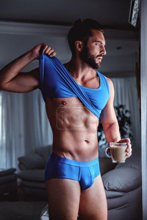 Bearded man holding coffee and undressing