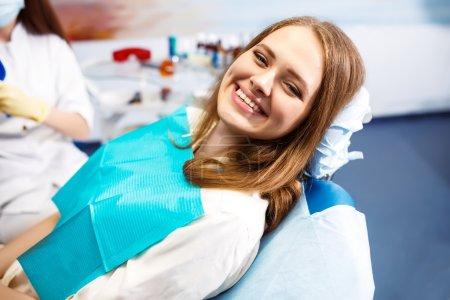 Photo pour Aperçu de la prévention de la carie dentaire.Femme à la chaise du dentiste pendant une intervention dentaire. Belle femme sourire de près. Souriez sainement. Belle sourire féminin - image libre de droit