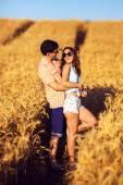 Pár v lásce těší baret při západu slunce. Emocionální pojetí vztahu s cestovní přítel a přítelkyně relaxační dohromady