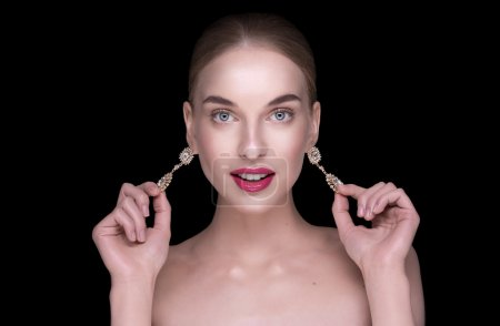 beautiful girl holding earrings