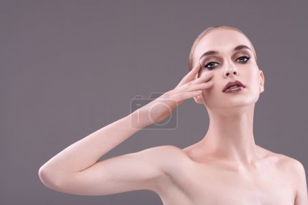 Blonde with arm raised in the evening make-up looking at the cam