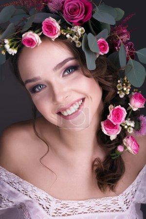 Foto de Chica mirando a la cámara muestra una bella composición de rosas artesanales y otras plantas - Imagen libre de derechos