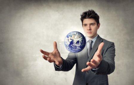 Photo pour Jeune homme d'affaires avec la planète qui flotte hors des mains - image libre de droit