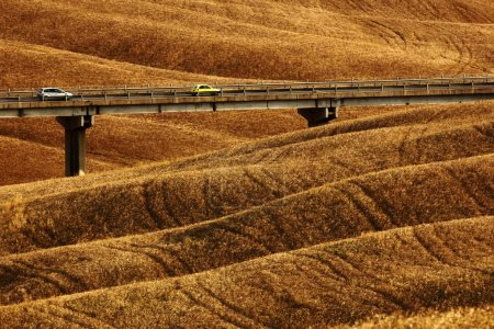 Cars on bridge between fields
