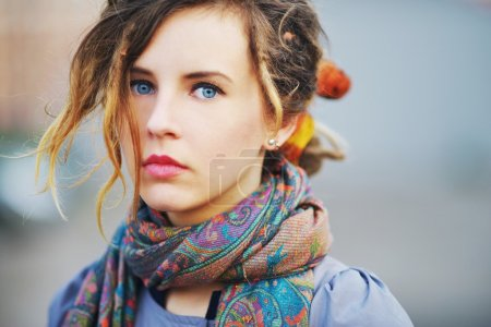 Gorgeous portrait of a young serious girl with beautiful blue eyes and youthful hair in the scarf   color picture, closeup.