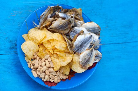 Photo for Close up of  the mix beer snacks on wooden background. Potato chips, roasted and salted peanuts, dried fish in blue plate on the blue wood background.Top view - Royalty Free Image