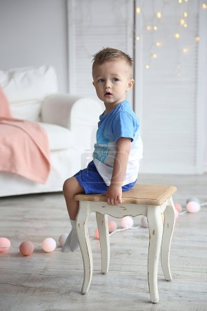 Cute little boy sitting on a chair in decorated room