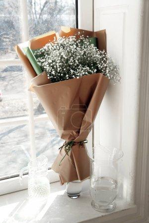 Photo pour Un bouquet de gypsophila en emballage artisanal dans un vase sur la fenêtre - image libre de droit