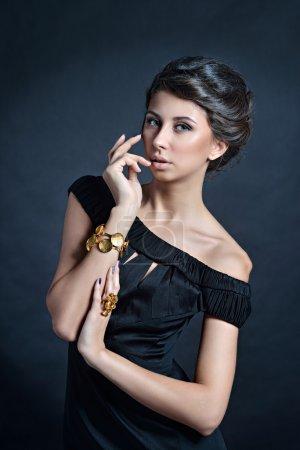 Photo pour Belle jeune fille brune en robe noire et des bijoux élégants posant sur fond foncé - image libre de droit