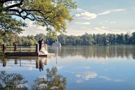 Beautiful bride and groom near lake