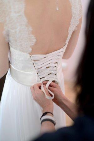 Bridesmaid lacing white wedding dress