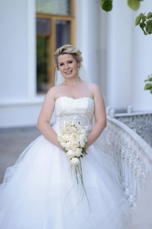 Photo for Beauty blonde bride in bridal gown with bouquet and lace veil posing near white building. Beautiful model girl in a white wedding dress. Woman with hairstyle. Cute lady outdoors - Royalty Free Image