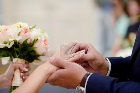 Photo pour Mariés portant des bagues l'un l'autre. Couple de mariage à la cérémonie de mariage. Belle fille en robe blanche et homme en costume - image libre de droit