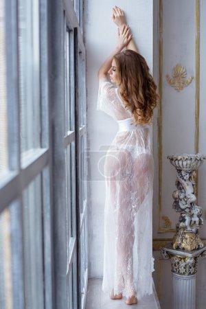 Photo pour Belle dame sexy dans une robe blanche élégante. Gros plan mode portrait du modèle à l'intérieur. Beauté femme blonde avec un corps attrayant en lingerie dentelle - image libre de droit