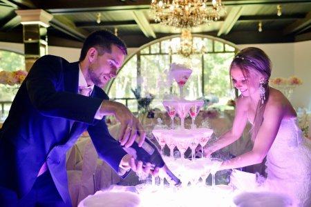 Photo pour Beau couple de mariage versant du champagne à l'intérieur. Verres colorés pour l'alcool avec des baies pour mariée et marié. Beauté de l'intérieur nuptiale pour le mariage. Bar lumineux pour la célébration - image libre de droit