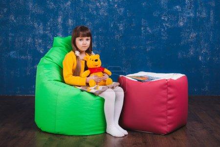 Photo pour Meubles rembourrés. Un enfant avec des jouets et des livres sur un sac de la chaise - image libre de droit