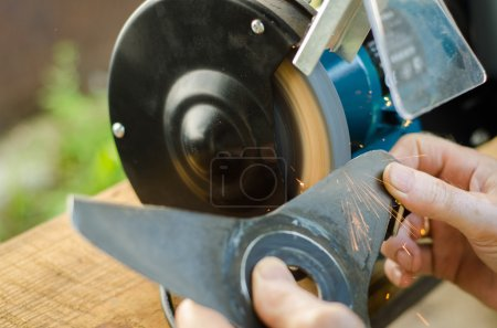 Photo for Worker sharpening his blade lawn mower. Flying sparks and work go well. - Royalty Free Image