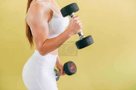 Photo for Athletic bodybuilder woman with dumbbells. Beautiful brunette girl with muscles lifting weights on yellow background - Royalty Free Image