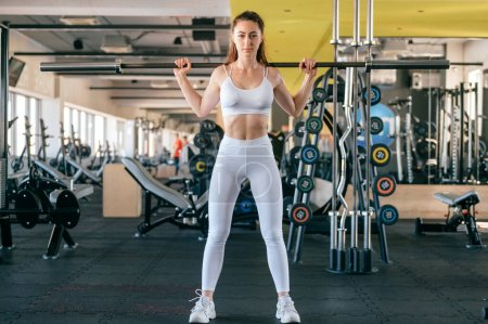 Photo for A young athletic girl does exercises using sports equipment in gym - Royalty Free Image