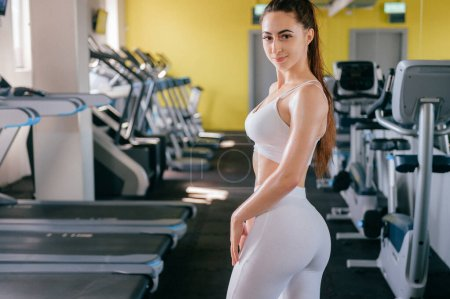 Photo for Portrait of athlete sexy girl in white sportswear posing in gym - Royalty Free Image