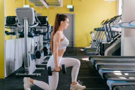 Photo for Muscular young woman with beautiful body doing exercises with dumbbell. Sporty girl lifting weights in gym - Royalty Free Image