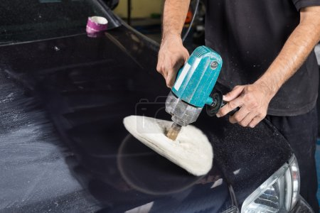 Car detailing series : Worker waxing blue car