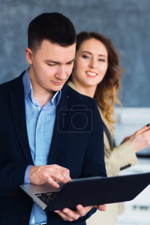 Shot of young businessman working on laptop with his partner.