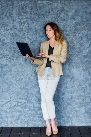Full length portrait of a happy young woman using laptop over gray background.